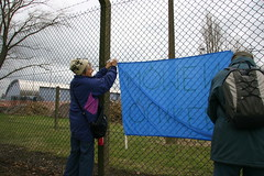 Women campaigners putting sign on fence