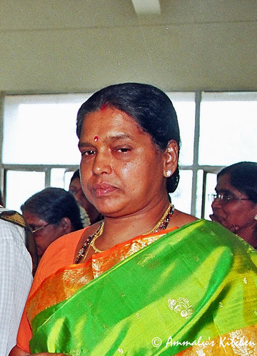 Amma , lost in thought and smiling to herself