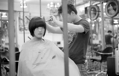 in the barber's (Salmonpink) Tags: blackandwhite bw reflection girl blackwhite women shenzhen barbers sbe salmonpink summicron50mm leicamp 123bw leicasummicron50mmf20v throughamirror China:City=shenzhen