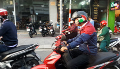 No-hands phone (Roving I) Tags: nohands chatting cellphones helmets motorcycles motorbikes traffic communications street danang technology vietnam