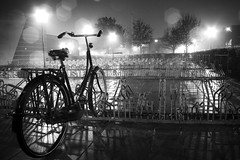 Wet and Alone (winkeh) Tags: light bw holland rain bike bicycle night canon dark licht alone zwartwit nacht empty nederland thenetherlands spots canoneos350d regen fiets donker alleen woerden fietsenstalling leeg batavus anawesomeshot petersparks