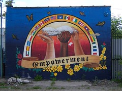 a mural on a free-standing brick wall. blue background with butterflies. and arch with flags from many countries.  in the arch, three hands hold up a book. one hand is white, another black, and a third yellow.  along the bottom there are flowers and the word 'empowerment'
