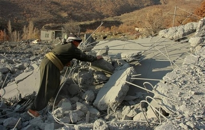 A villager looks through a rubble at the Qlatooka village near Iraq's border with Turkey on Sunday Dec 16 2007