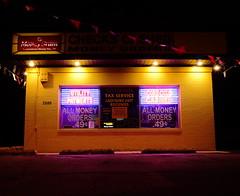Currency Exchange (animefx) Tags: camera city longexposure urban color colour building night digital canon eos illinois neon flags business springfield dslr 2009 ff currencyexchange moneyorders 35mmf2 sangamoncounty taxservice 5dmarkii 5d2 5dmkii 5dmk2 5dmark2