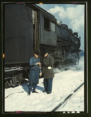 Atchison, Topeka, and Santa Fe railroad conductor George E. Burton and engineer J.W. Edwards comparing time before pulling out of Corwith railroad yard for Chillicothe, Illinois; Chicago, Ill.  (LOC) (The Library of Congress) Tags: snow chicago santafe train geotagged march illinois sand 4x5 locomotive libraryofcongress kodachrome chillicothe topeka engineer cookcounty 1943 atchison steamlocomotive chicagoil comparing corwith jackdelano xmlns:dc=httppurlorgdcelements11 march1943 chillicotheil dc:identifier=httphdllocgovlocpnpfsac1a34701 georgeeburton jwedwards geo:lat=41810428 geo:long=87715026