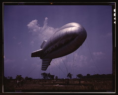 Parris Island, S.C., barrage balloon  (LOC) (The Library of Congress) Tags: blue sky sc field silver t island quiet gloomy purple aircraft south ballon wwii balloon flight may caroline southcarolina zeppelin dirigeable surreal tint palmer cables helium blimp carolina airship nostalgic daytime alfred midair libraryofcongress 1942 ropes tethered marinecorps hydrogen dirigible specialdelivery ginourmous parris parrisisland airframe lowhorizon guywire airdefense trainingschool beaufortcounty mooringropes thehumanity barrageballoon xmlns:dc=httppurlorgdcelements11 dc:identifier=httphdllocgovlocpnpfsac1a35101 alfredtpalmer barrageballoongroup a2fp