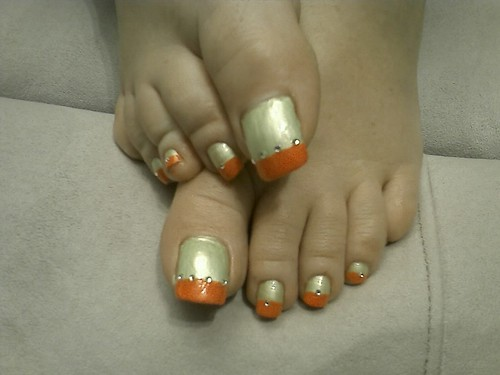 Long toenails in silver orange nail art design