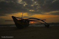 The sunsets as a catamaran awaits its crew for the nights catch (charithra Hettiarachchi) Tags: sunset red sea colour beach eos boat fishing sand waves catamaran canon flickrsbest sri lanka golddragon mywinners 400d theperfectphotographer charithra hettiarachchi glodendragon