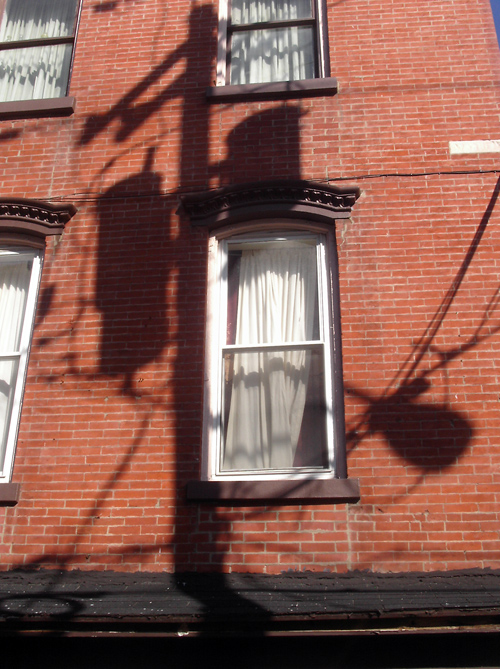 shadow of transformer on brick building