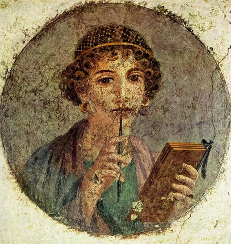 Pompeiian fresco of Sappho by an unknown artist, via laits.utexas.edu, which describes the fresco as: A young woman holding a stylus and a booklet of wax tablets. A gold hair net binds her hair and she wears large, gold earrings.
