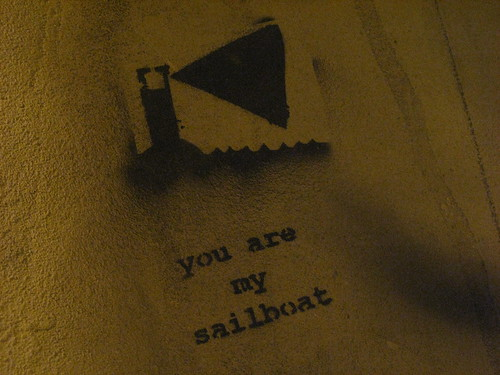 stencil graffiti of a lighthouse shining a triangle of light out over water, with the words, 'you are my sailboat'