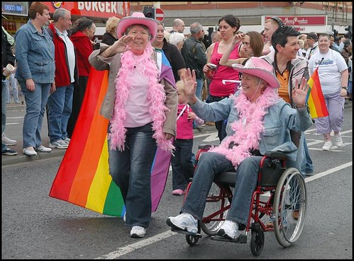 A wheelchair user and a walker, both wearing matching cowboy hats and pink feather boas. The walker is wearing a gay pride flag as a cape.