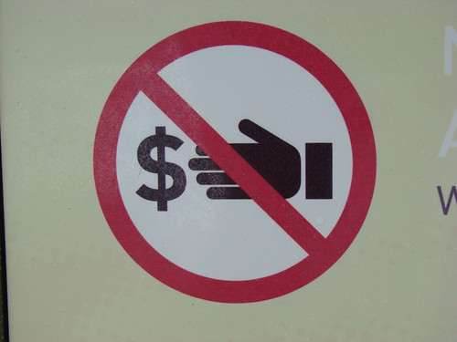 a sign depicting a hand reaching for money with a slash through it