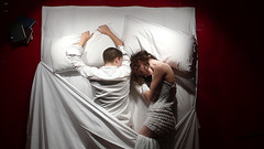 two people in bed (micheeky) Tags: leica sleeping red two people woman white man men london window public face shirt still bed movement hands pants heart emotion display sleep performance performing dream down books guys valentine sheets clothes pillow gloves lacy bookshop michiru vd dlux3 micheeky