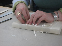 Threading leather thongs through vellum