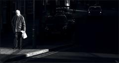 Light Paths (Jim Blob Blann) Tags: street old morning light bw sun sunlight white man black cars car wales canon dark bag walking town darkness path beam aberystwyth elderly shard 400d