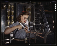 Operating a hand drill at the North American Aviation, Inc., [a] woman is in the control surface department assembling a section of the leading edge for the horizontal stabilizer of a plane  (LOC)
