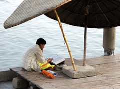 india (gerben more) Tags: people india water umbrella river reading prayer study varanasi ganges benares holybook