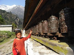 Girl turning prayer wheels