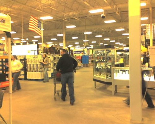 a customer walking into sams club with a cart