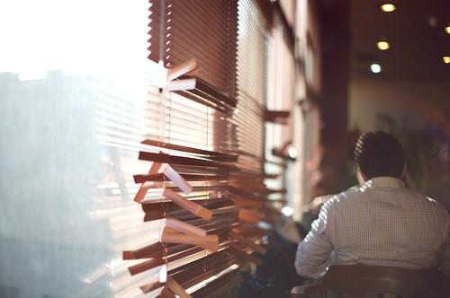 Fotografía de la clásica persiana de plástico reventada en los extremos, al fondo un hombre está sentado iluminado por la luz que pasa por las persianas