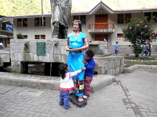 niños juegan alrededor de estatua