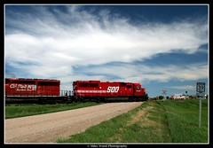 A Prairie Level Crossing, 2007 (Mike Wood Photography) Tags: road railroad blue red sky canada green clouds train eos engine location canadian arr mysterious locomotive prairies allrightsreserved levelcrossing mikewood emdsd402 400d aplusphoto mikewoodphotographycom emdsd60 mikewoodphotography soo6056 cprail5995 mwptrav