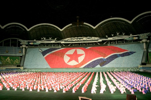 a political rally in north korea with giant flag