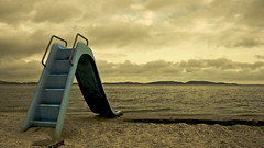 no one to play (fabiogiolito) Tags: blue sea sky praia beach playground yellow azul clouds landscape mar sand brinquedo areia paisagem cu nuvens spa sopedrodaaldeia escorrega