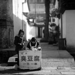 gateway (memetic) Tags: china street bridge girls bw 120 6x6 mediumformat blackwhite fuji crossing dof bokeh tl tofu stall neopan  stinky shaoxing zhejiang acros p6  pentaconsix sonnar   180mm  doufu