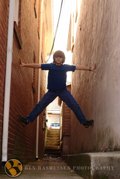 Kid suspending himself in an alley