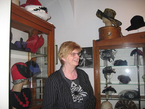 Picture of Tiny Meihuizen-Wijker, owner of the museum, in front of the hats she has made herself