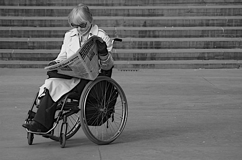 A black and white image of a wheelchair user reading a newspaper on Trafalgar Square, London.