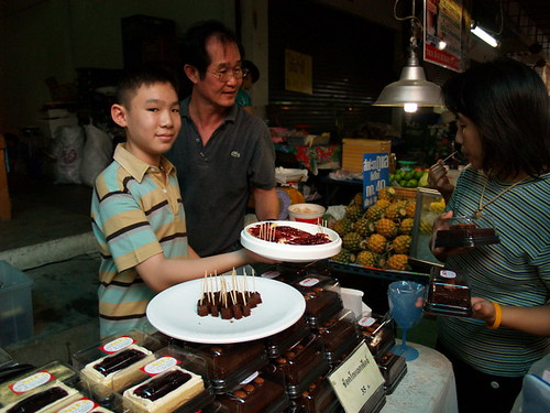 In a Thai market, a boy offers samples of his wares for the passersby.