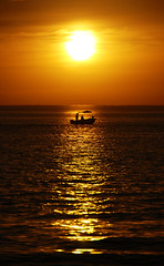 fishing in the light of the setting sun (Janet Leadbeater) Tags: ocean light sunset sea orange sun man color colour men water silhouette yellow clouds golden boat fishing setting