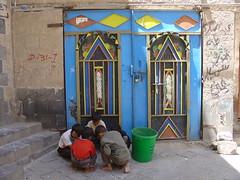 Children playing before a modern iron door in Sanaa (olga_rashida) Tags: door children kinder yemen sanaa supershot 10faves 5photosaday jemen anawesomeshot aplusphoto isawyoufirst diamondclassphotographer flickrelite theunforgettablepictures excapture
