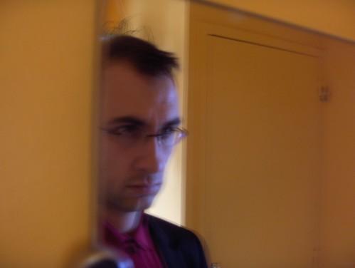 Autoportrait miroir au polo rouge boutonné et aux murs jaunes