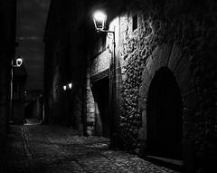 Santillana del Mar by night, Spain, March 2016 (Juha Riissanen) Tags: spain santillanadelmar bw night medieval lamps dark cobblestones gate alley narrow
