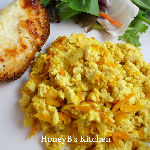 Scrambled Tofu on a plate with salad and cheesy garlic bread