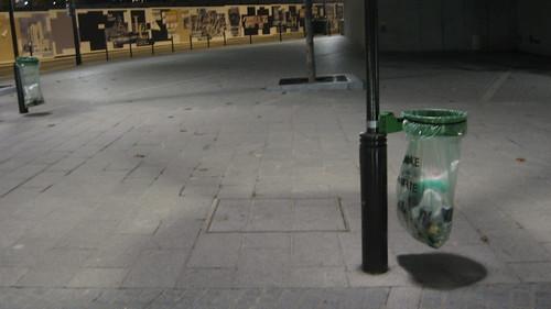 Fotografía de una papelera típica de París, que no tiene más que un bastidor de metal sobre el que cuelga la bolsa de plástico traslúcida