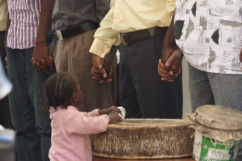 One of the staff's daughters watches by the drum as the translators pray