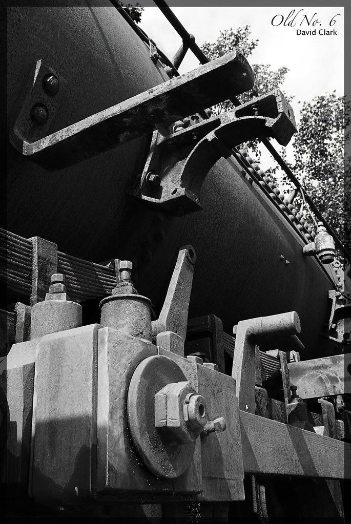 An old steam engine, with many rusted parts, viewed at a sharp angle from the side.