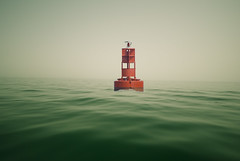 buoy (benoit pinon) Tags: old red sea green classic beach water colors beautiful yellow metal fog vintage lost nice waves mood alone quiet sad no nowhere barrel platform deep floating wave device calm lonely middle oman lifebuoy channel buoy brume anchored boue navigational bouee buoyant