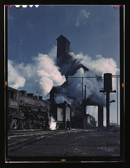 Locomotives over the ash pit at the roundhouse and coaling station at the Chicago and Northwestern Railroad yards, Chicago, Ill.  (LOC) (The Library of Congress) Tags: railroad blue chicago history train geotagged jack illinois smoke trains steam locomotive libraryofcongress 1942 steamengine locomotives cookcounty delano chicagoillinois colorphotograph chicagoandnorthwestern historicalphoto jackdelano xmlns:dc=httppurlorgdcelements11 dc:identifier=httphdllocgovlocpnpfsac1a34645 40thstyard geo:lat=41888661 geo:long=87727316