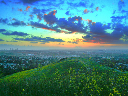 Sunset behind a cloud over the Pacific Ocean from French Hill Turtle Rock Irvine California looking West , Newport Center highrise buildings to the left on the horizon, University of California at Irvine in the center midground. clouds blue orange green