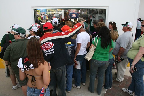 Human aquarium. Fans gather around a window into a garage bay where a crew works on a car.