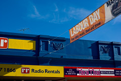 Colours of Brisbane: Shopfronts in Wickham Street and Labour Day (Craig Jewell Photography) Tags: blue red sky cloud color colour yellow buildings iso100 colorful day banner brisbane f90 valley shops labour colourful stores shopfront fortitudevalley 1125sec pentaxk10d smcpentaxfa35mmf2al cpjsm craigjewellphotography