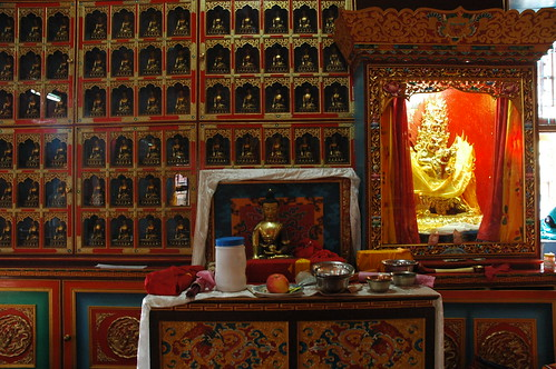Cases of Buddhas, Buddha in the lama's seat, book (pecha), fruit, incense, Vajrakilaya statue in ornate lit case, fancy Tibetan style monastery painting and decor, Sakya Monastery, Pharping, Nepal by Wonderlane