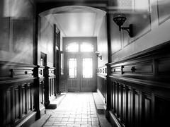 En port i Vasastan (gothicburg) Tags: light bw reflection göteborg sweden gothenburg entrance eerie spooky vasastan 080506 olympusc5050z monochromia lightfromwithin throughcloseddoor