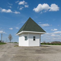 Small slope-roofed building with siding and windows, upon a concrete platform in a gravel setting. (Tim Kiser) Tags: 2015 20150429 april april2015 centertownship centertownshipmonroecountyohio centertownshipohio highway26 img5981 monroecounty monroecountyfairground monroecountyfairgrounds monroecountyohio ohio ohio26 ohioroute26 ohiostateroute26 route26 statehighway26 stateroute26 woodsfield woodsfieldohio building countyfairgrounds cumulus cumulusclouds eastohio easternohio electriclines electricpoles fairground fairgrounds gravel mostlysunny outbuilding overheadelectriclines overheadpowerlines potholes powerlines ptichedroof siding slopedroof smallbuilding southeastohio southeasternohio steeproof telephonepoles utilitypoles whitesiding windows unitedstates